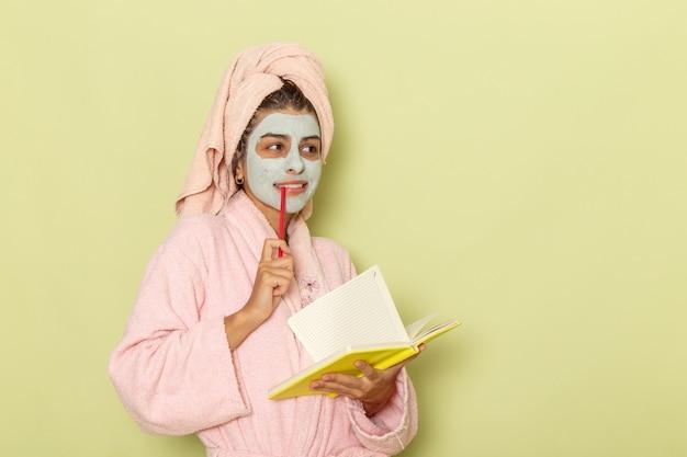 Giovane femmina di vista frontale in accappatoio rosa che annota le note che pensano su una superficie verde