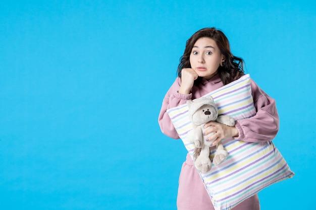 Vista frontale giovane donna in pigiama rosa su notte blu