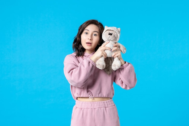 Front view young female in pink pajamas with little toy bear on blue