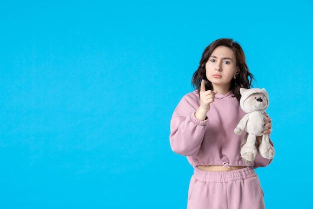 Vista frontale giovane donna in pigiama rosa con piccolo orso giocattolo su blue
