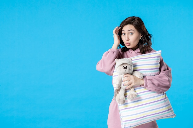 Front view young female in pink pajamas with toy bear and pillow on blue