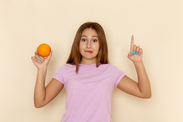 Front view young female in pink t-shirt and blue jeans holding orange with confused expression
