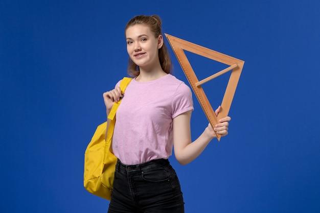 Vista frontale di giovane donna in maglietta rosa che tiene la figura di triangolo di legno sulla parete blu