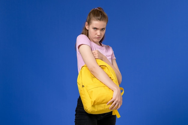 Front view of young female in pink t-shirt holding yellow backpack on blue wall