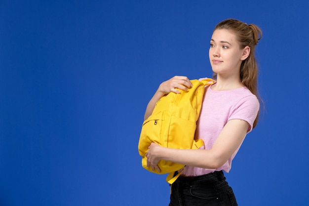 Front view of young female in pink t-shirt holding yellow backpack on the blue wall