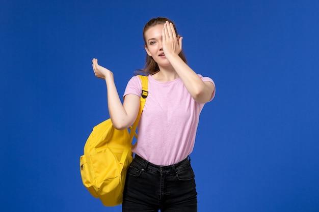Vista frontale della giovane donna in maglietta rosa che indossa uno zaino giallo chiudendo metà del suo viso sulla parete azzurra