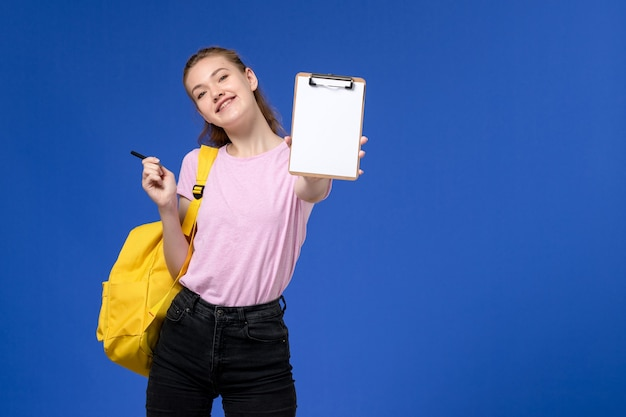 Front view of young female in pink t-shirt wearing yellow backpack and holding notepad on the blue wall