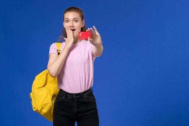 Vista frontale della giovane donna in maglietta rosa che indossa lo zaino giallo che tiene il cartellino rosso di plastica sulla parete blu