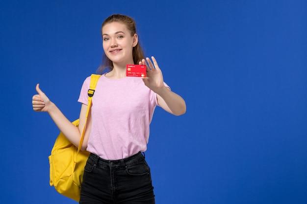 Vista frontale di giovane donna in maglietta rosa che porta zaino giallo che tiene cartellino rosso di plastica che sorride sulla parete blu