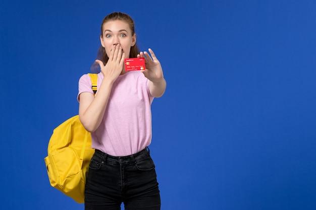 Vista frontale della giovane donna in maglietta rosa che indossa lo zaino giallo che tiene il cartellino rosso di plastica