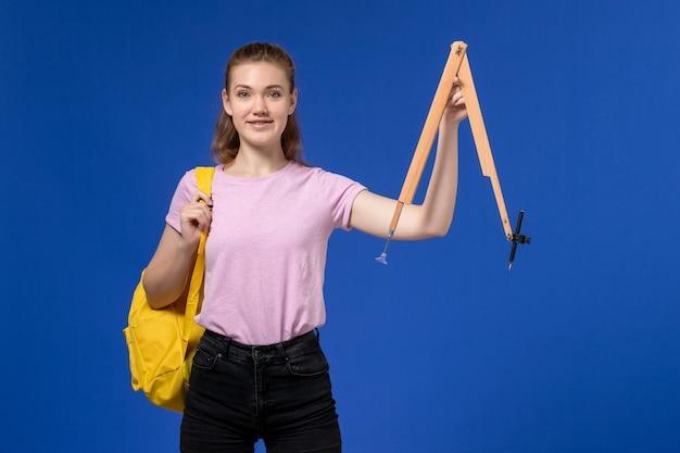 Vista frontale della giovane donna in maglietta rosa che indossa uno zaino giallo che tiene la figura di legno sulla parete blu