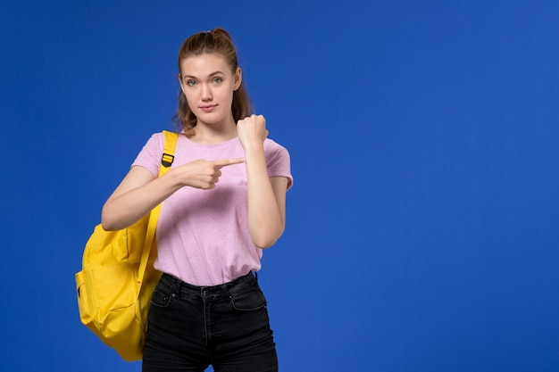 Front view of young female in pink t-shirt wearing yellow backpack showing her wrist on the light-blue wall