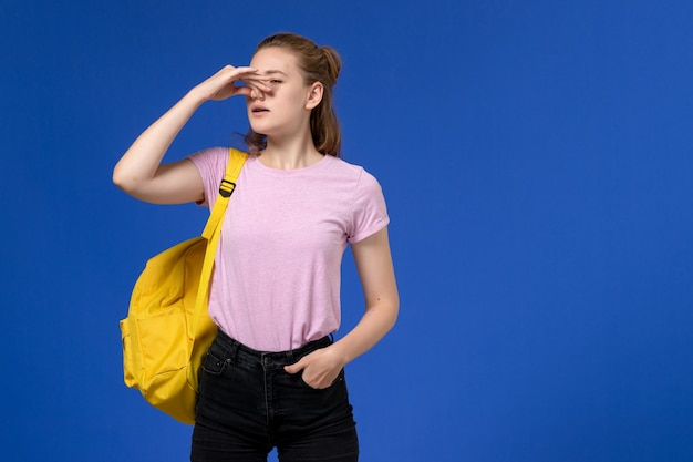 Front view of young female in pink t-shirt wearing yellow backpack shutting her nose on the light-blue wall