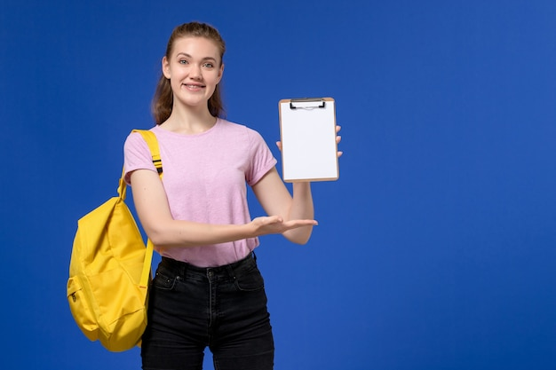 Front view of young female in pink t-shirt wearing yellow backpack smiling and holding notepad on blue wall