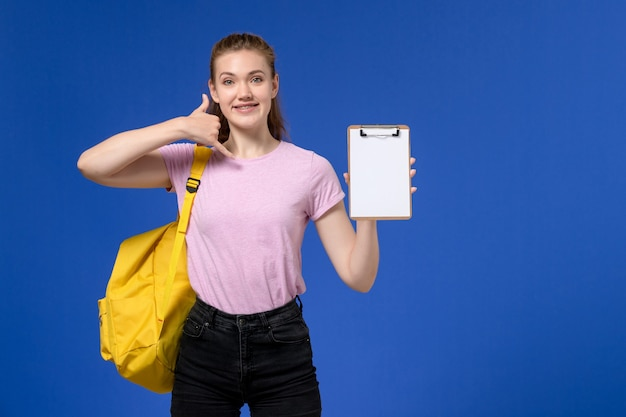 Front view of young female in pink t-shirt wearing yellow backpack smiling holding notepad on blue wall