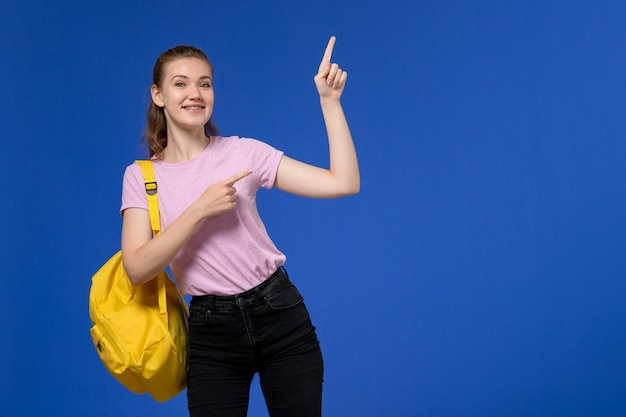 Front view of young female in pink t-shirt wearing yellow backpack smiling on light blue wall