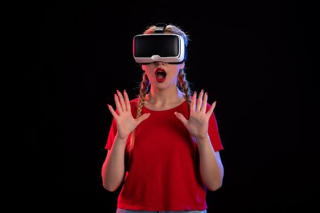 Vista frontale di una giovane donna che gioca con la realtà virtuale su ultrasuoni visivi scuri