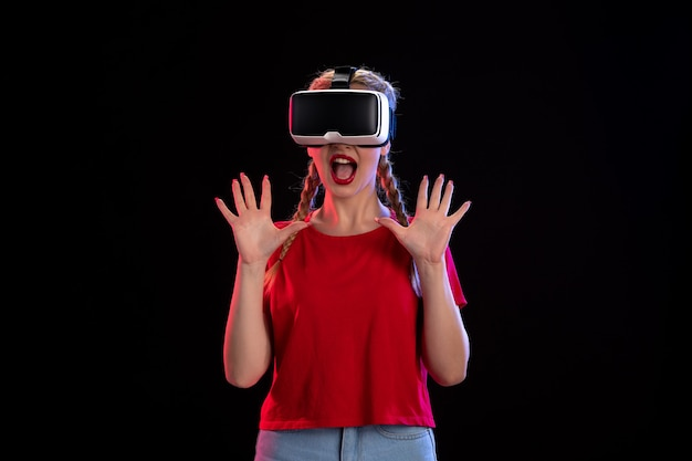 Front view of young female playing virtual reality on dark wall
