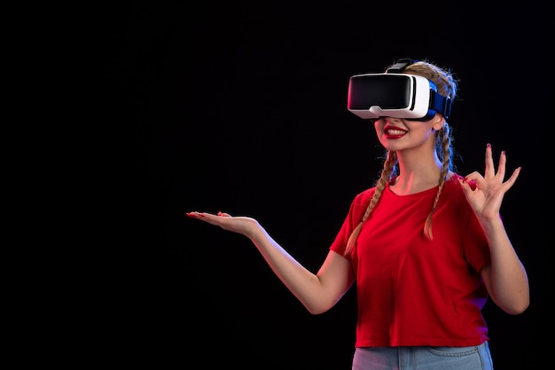 Vista frontale della giovane donna che gioca vr sul pavimento scuro gioco ad ultrasuoni visual tech d