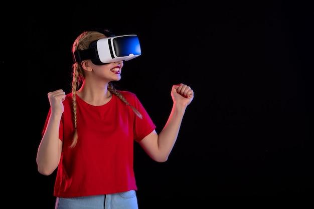 Vista frontale della giovane donna che gioca vr sulla fantasia ad ultrasuoni del gioco oscuro dark
