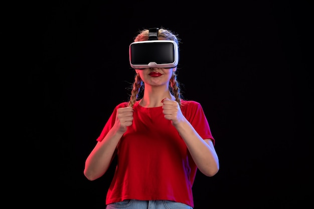 Front view of young female playing vr on a dark wall