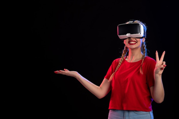 Front view of young female playing vr on dark wall