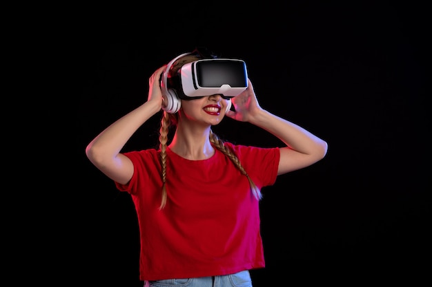 Front view of young female playing vr in headphones on a dark wall