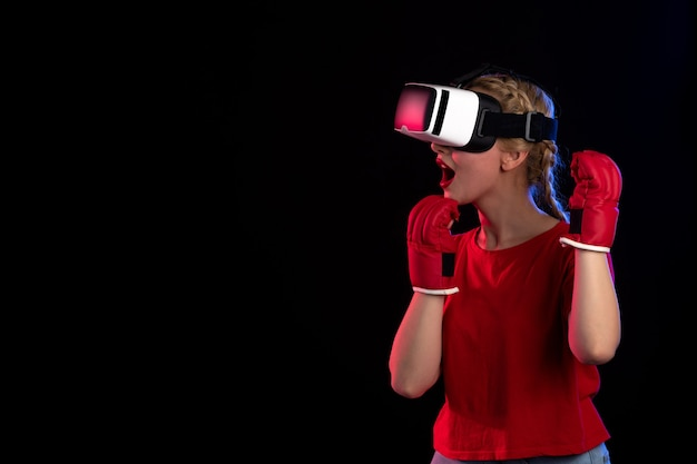 Front view of young female playing vr in mma gloves on a dark wall