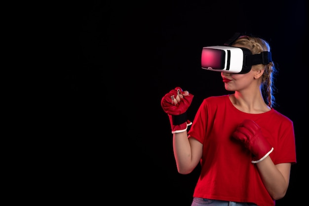 Front view of young female playing vr in mma gloves on dark wall