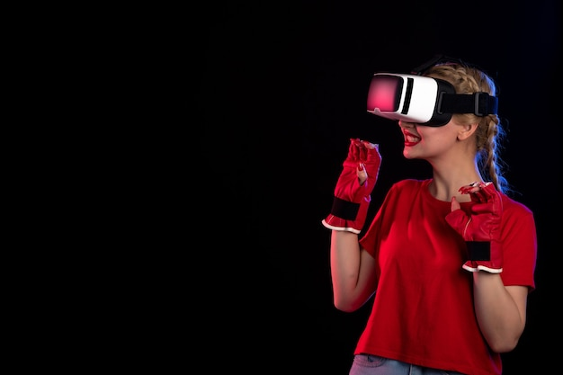 Front view of young female playing vr in mma gloves on the dark wall