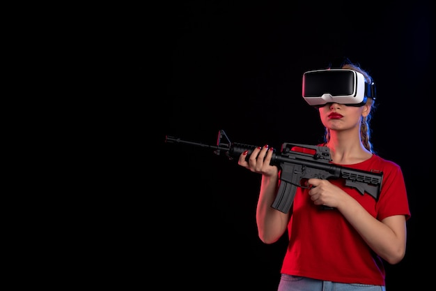 Front view of young female playing vr with toy rifle dark wall