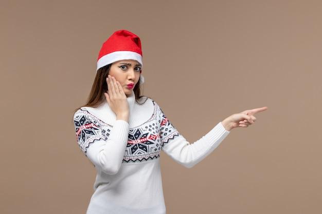 갈색 책상 감정 크리스마스 새 해에 빨간 모자에 포즈 전면보기 젊은 여성
