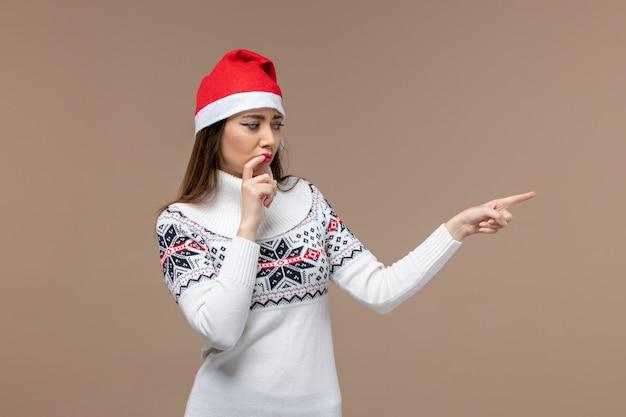 어두운 갈색 배경 감정 크리스마스 새 해에 빨간 모자에 포즈 전면보기 젊은 여성