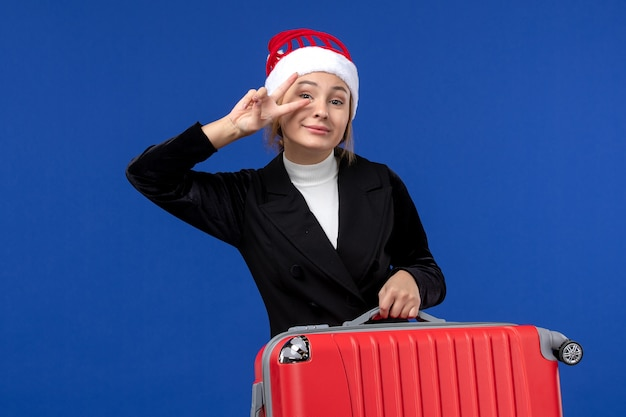 Giovane femmina di vista frontale in posa e sorridente sulla donna di vacanza di vacanza della parete blu