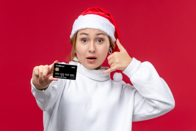 Front view young female posing with bank card on a red background
