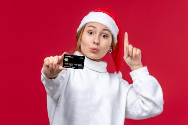 Vista frontale giovane femmina in posa con carta di credito su sfondo rosso