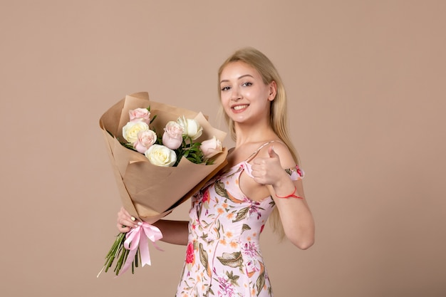 Front view of young female posing with bouquet of beautiful roses on brown wall