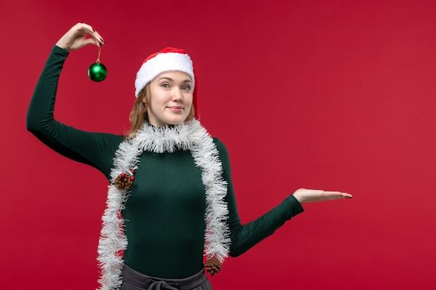 Вид спереди молодая женщина позирует с новогодними атрибутами на красном фоне
