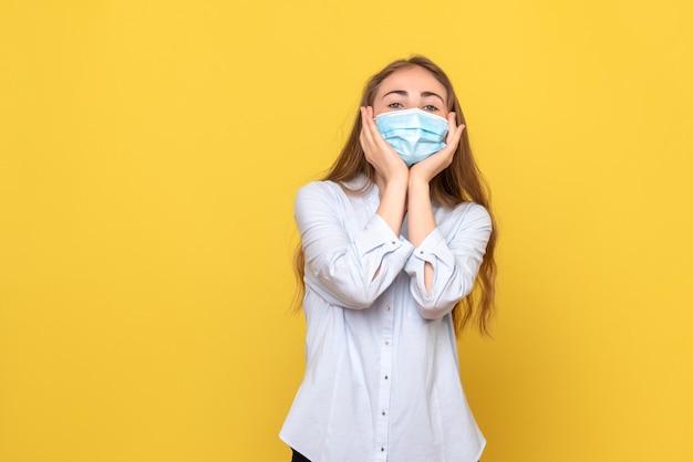 Vista frontale della giovane donna in posa sul muro giallo
