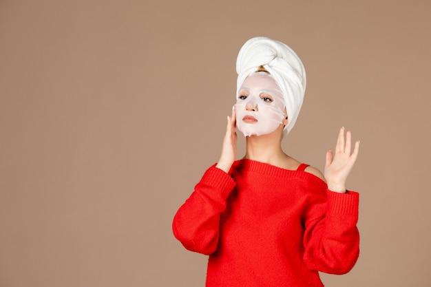 Vista frontale giovane femmina si prepara ad applicare la maschera per il viso su sfondo rosa