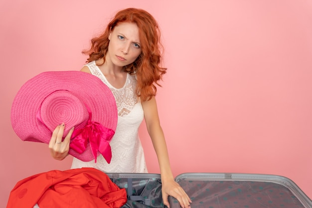 Vista frontale della giovane donna che si prepara per i vestiti per il viaggio sulla parete rosa