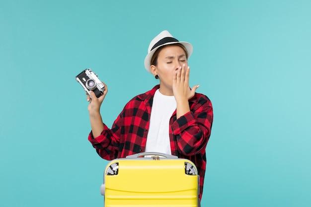 休暇の準備をし、青い空間であくびをしている写真カメラを保持している正面図若い女性