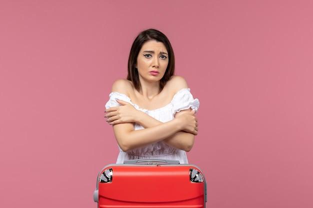 Вид спереди молодая женщина готовится к отпуску и дрожит на розовом фоне поездка путешествие путешествие отпуск женщина за границу