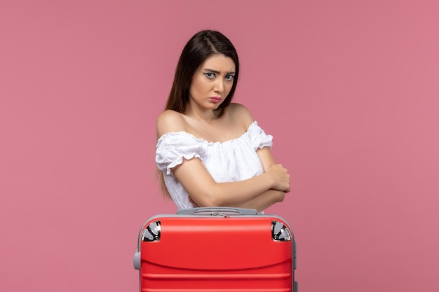 Вид спереди молодая женщина готовится к отпуску и дрожит на розовом фоне.