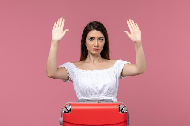 明るいピンクの背景で休暇の準備をしている正面図若い女性海外旅行旅行航海