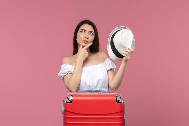 淡いピンクの背景で休暇の準備をしている正面図若い女性海外旅行海の旅の航海