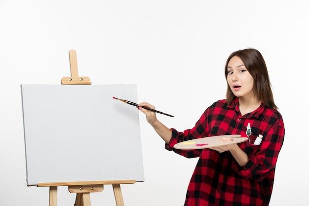 흰 벽 미술 전시회 그림 그리기 예술가 술에 이젤에 페인트 브러시로 그릴 준비 전면보기 젊은 여성