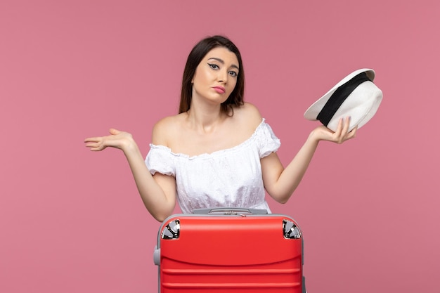 Front view young female preparing for vacation on a pink background journey travelling sea trip abroad voyage