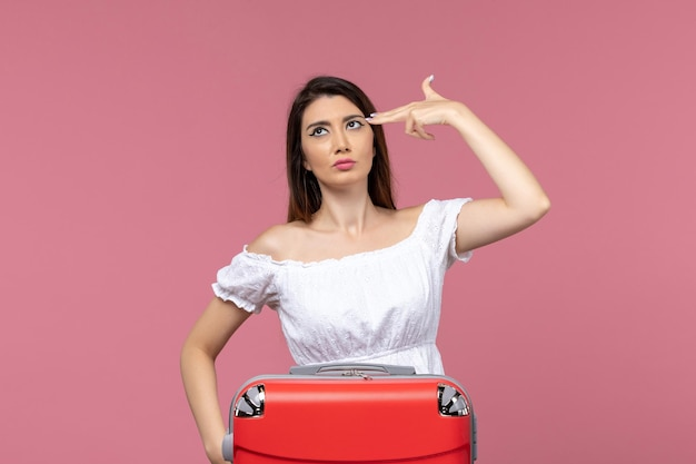 Front view young female preparing for vacation on the pink background trip travel voyage vacation woman abroad
