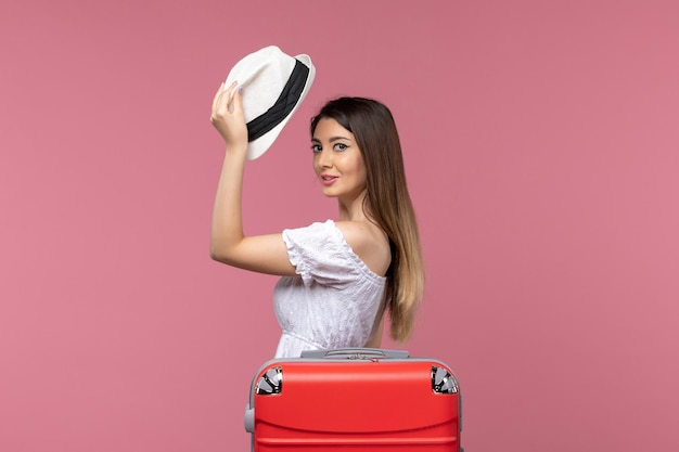Front view young female preparing for vacation on the pink background voyage trip journey abroad travel sea